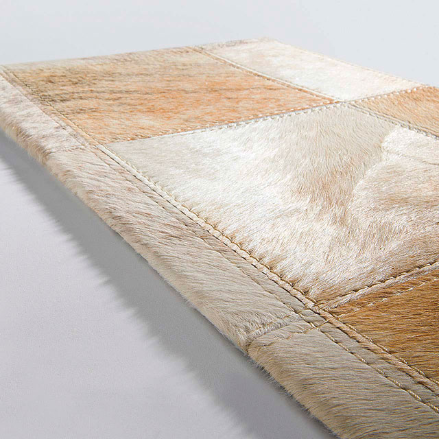 edge view: the finished edge of a pinto leather area rug (color sable)